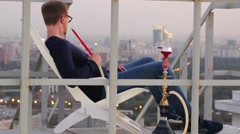 Man reclining in chair, smoking hookah pipe from watching panorama of city Stock Footage