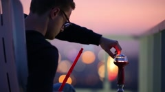 Guy with pipe in his hand covering with cap of hookah coals on roof Stock Footage