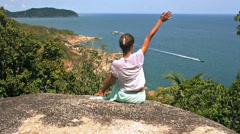 Young woman is waving boat sitting on a high stone Stock Footage