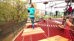 Girl walking with climbing protection by boards hanging above ground Stock Footage