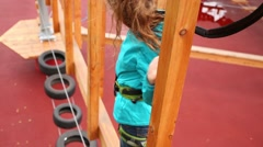 Girl going on wooden bar with pillars in ropes park. Stock Footage