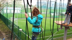 Girl moving sideways on rope, holding on to cross ropes in ropes park Stock Footage