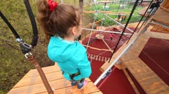 Girl going to walk on beam suspended on ropes, standing on platform Stock Footage