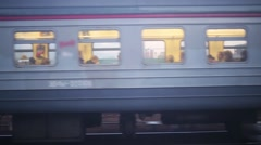 Wagons of train with passengers inside, going on railways at dusk. Stock Footage