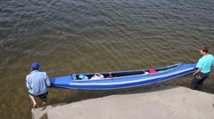 Two men lowered boat into water of river from mooring on river Stock Footage