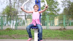 Girl raising herself sitting on street exerciser pushing up handle. Stock Footage