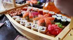 Close up of wooden boat-plate with variety of sushi on table Stock Footage