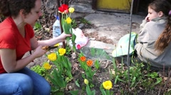 Women squatting cutting tulips and poppies and beside two girls sitting Stock Footage