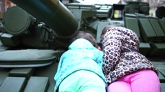 Two girls are considering tank armor lying on it on streets of Samara Stock Footage