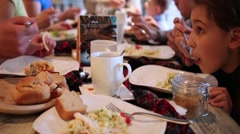 Children and adults eating and drinking at same table in restaurant. Stock Footage