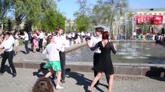 Teens in dresses and costumes dance at fountain in Samara Stock Footage