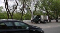 Cleaning machine small goes on road through city and close to cars. Stock Footage