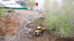 Yellow bulldozer with scoop leveling ground on banks of Volga River. Stock Footage