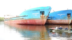 Row of old rusting decommissioned tanker VolgaOil and three men in boat Stock Footage