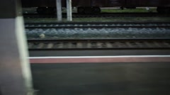 Low station platform with few people on it, next to rails flash in darkness. Stock Footage