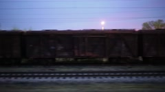 Wagons on tracks, platform at station and people moving at dusk. Stock Footage