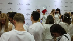 People in white photographing against background of banner Sensation Stock Footage