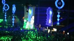 Bald DJ in headphones on screen above dancing people in dark Stock Footage