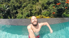 Young happy man recording selfie video in swimming pool Stock Footage