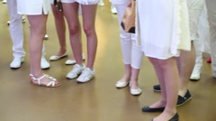 Legs of people wearing white clothes and shoes, standing and walking Stock Footage