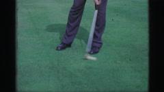 1968: Man putting golf balls on practice green bulleye putter club. CEDAR Stock Footage