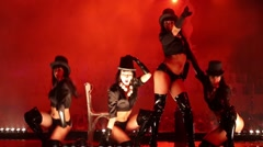 Four girls in black posing on stage at red light at Olympic Stadium Stock Footage