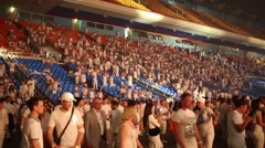 Rows of seats with audience dancing in white at Olympic Stadium Stock Footage