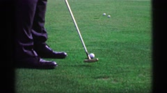 1968: Slow motion man putting golf balls on practice green with bullseye putter - stock footage