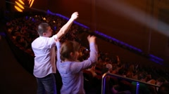 Boy and girl waving hands in back row in Crocus city hall Stock Footage