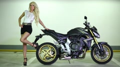 Blonde woman posing next to purple sport motorcycle. Stock Footage