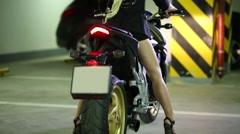 Woman blonde sitting in helmet on motorcycle, turn off headlight. Stock Footage