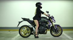Woman sitting on sports bike, putting and removing hands from rudder. Stock Footage