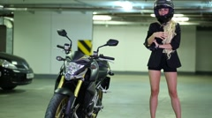 Woman with slim legs and helmet wearing gloves near motorcycle Stock Footage