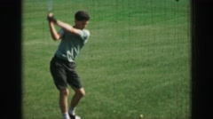 1968: Pre-teen boy hitting golf balls with driver club slow motion swing - stock footage