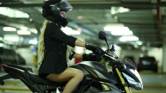 Woman on motorcycle closing visor helmet and putting hands on rudder. Stock Footage