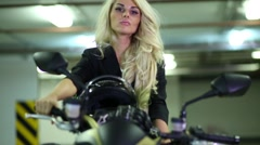 Woman correcting her hair sitting on motorcycle in underground parking Stock Footage
