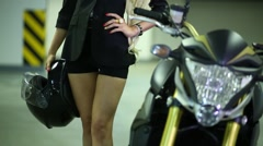 Torso of woman with long legs and helmet in hand next to motorcycle. Stock Footage