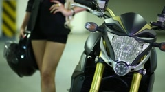 Woman with helmet next to motorcycle turning on and off headlight on it Stock Footage