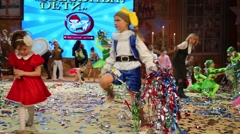 Little kids in costumes collecting colored tape on stage show Stock Footage
