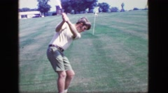 1969: Sideburns young man hits golf balls swing analysis towards practice pin. - stock footage