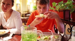 Boy eating pizza at table next to mother eating pasta in restaurant. Stock Footage