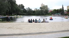 People sitting on sand at lake with catamarans in Gorky park. Stock Footage