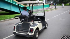 Man driving small electric car among rollers in park. Stock Footage