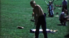 1969: Shirtless young boys practicing golf at driving range hitting balls - stock footage