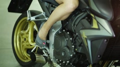 Long womens foot in heels on footboard of sports bike Stock Footage
