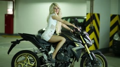 Blonde woman in white tank top and shorts sitting on sports bike Stock Footage