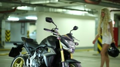 Blonde with helmets coming to motorcycle and turn on headlight. Stock Footage