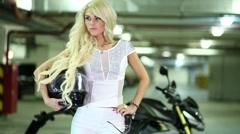 Luxurious blonde with helmet putting on dark glasses next to motorbike Stock Footage