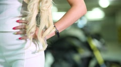 Hand with manicure on side of blonde woman in front of motorcycle. Stock Footage