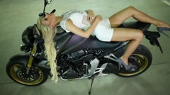Blond woman in white lying on sports bike and looking up. Stock Footage